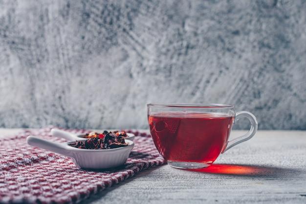 Tazza di tè con vista laterale di erbe di tè su uno sfondo grigio con texture