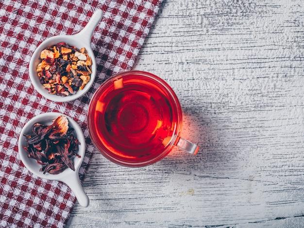 Tazza di tè con vista dall'alto di erbe di tè su un panno da picnic e fondo di legno grigio
