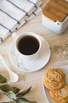 Cup of tea with teapot and breakfast elements