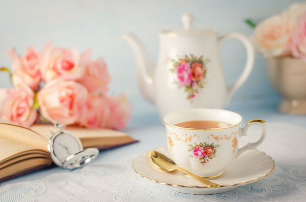 Cup of tea with teapot and flowers with vintage tone