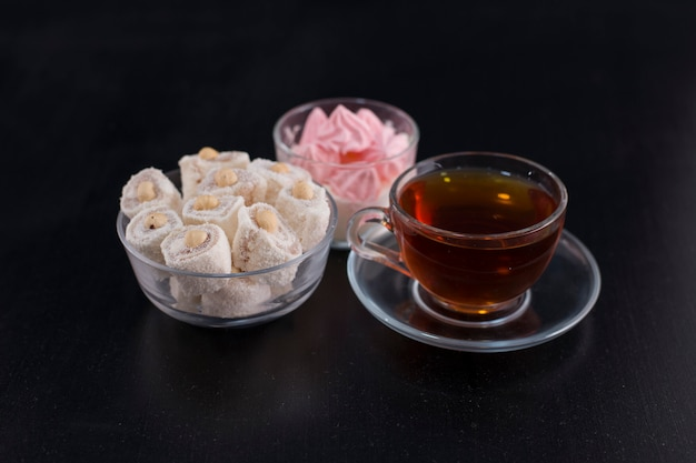 A cup of tea with turkish lokum and marshmallows in the center.