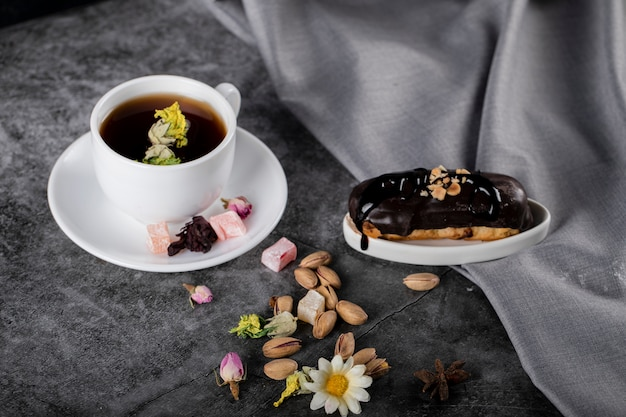 A cup of tea with turkish lokum, pistachios and chocolate eclair.