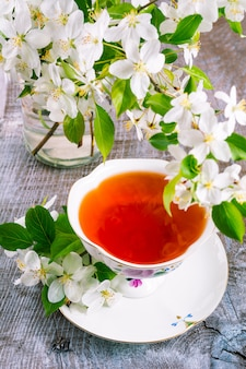 Cup of tea on wooden table and apple blossom