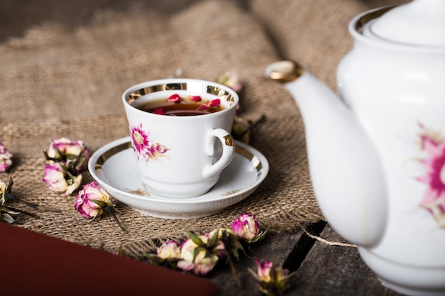 Cup of tea on wooden table with sackcloth