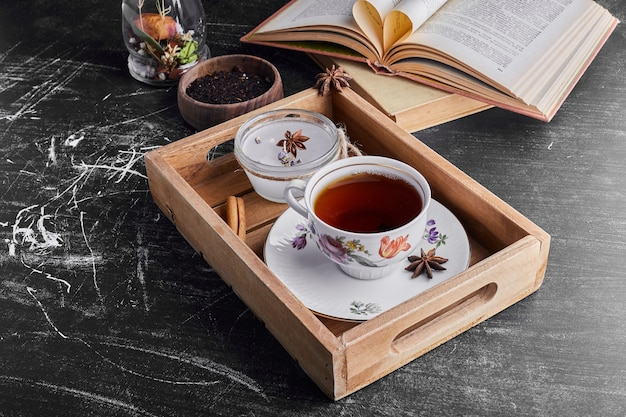 A cup of tea in a wooden tray.