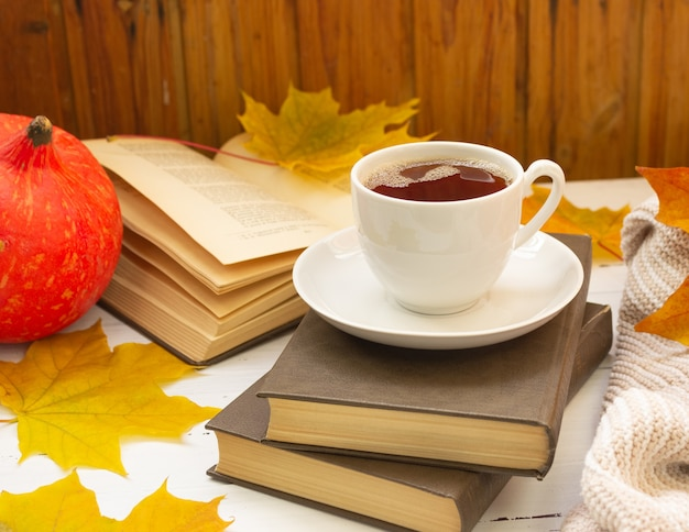 A cup of tea, yellow maple leaves, books, and a knitted thing