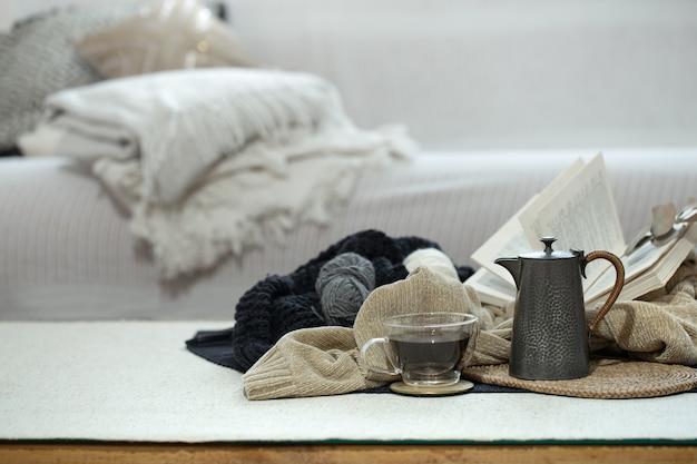 Чашка, чайник и книга на переднем плане в холодных тонах