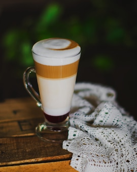 A cup of three layered latte with foam on top
