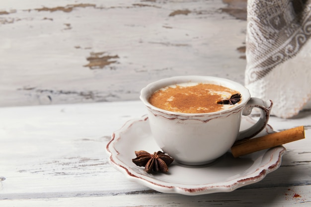Cup of traditional indian chai tea with star anise and cinnamon