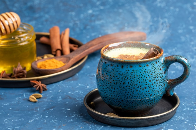 Cup of traditional indian hot drink golden turmeric milk with cinnamon, turmeric, anise and honey on blue background.