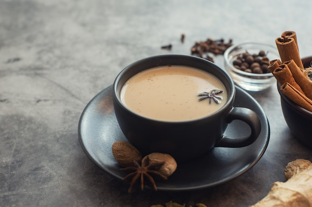 Cup of traditional indian masala chai tea with ingredients: cinnamon, cardamom, anise, nutmeg