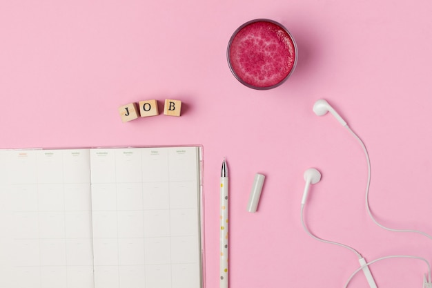 Cup of trendy superfood pink beetroot latte, pen, notepad