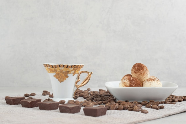Cup of turkish coffee coffee beans and chocolate on stone table