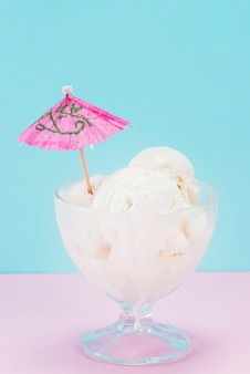 Cup of vanilla ice cream with paper umbrella on top