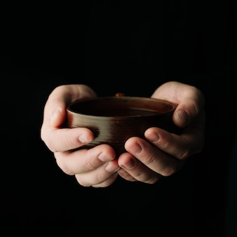 Cup of warm tea being held in hands