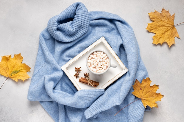Cup of warming drink with marshmallows and spices on cozy knitted sweater with yellow leaves