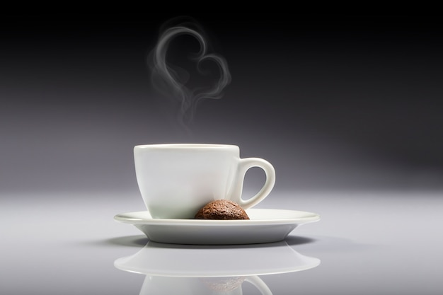 A cup of white coffee with a brown cookie and heart shaped smoke in a neutral background