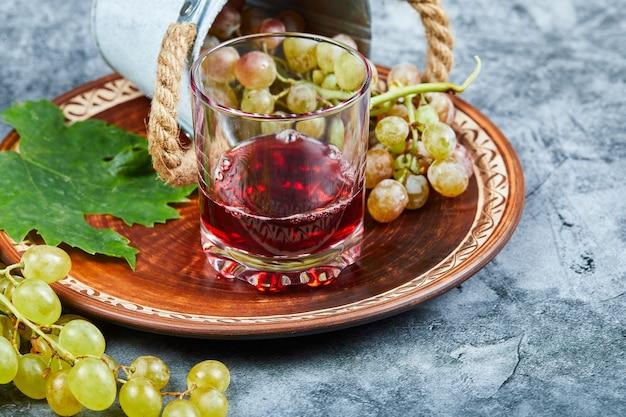 Una tazza di vino con grappoli d'uva intorno.