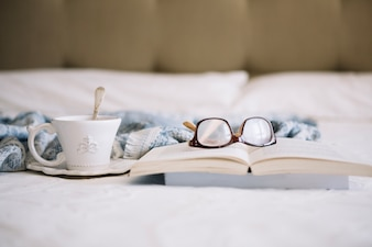 Cup with beverage near book and glasses