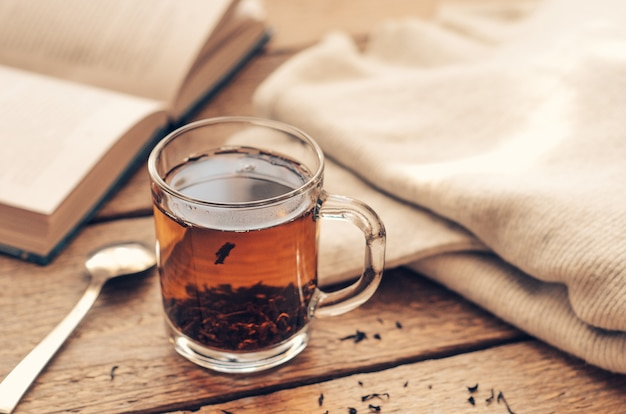 A cup with black brewed tea on a wooden table with book and a warm sweater