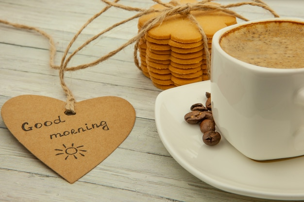 Cup with black coffee, coffee beans and ginger biscuits, healthy breakfast concept