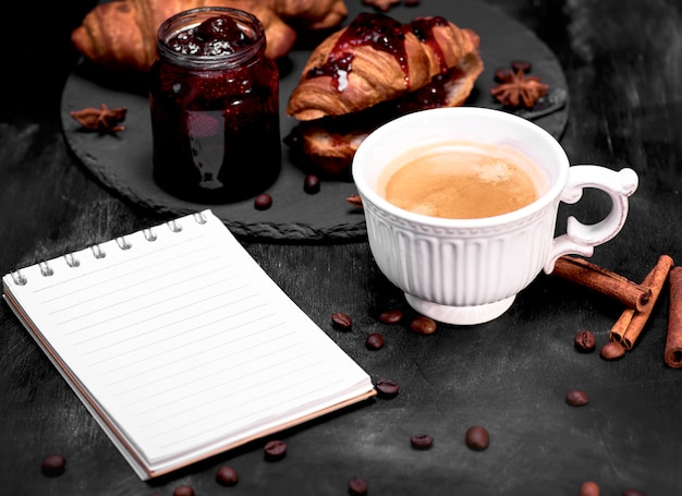 Cup with black coffee and an empty paper notebook