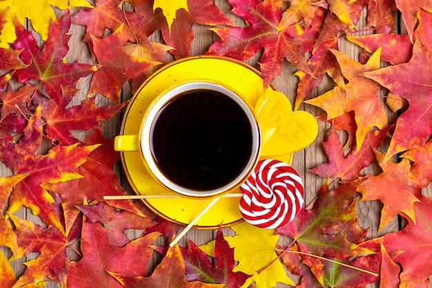 Cup with black coffee, red, yellow lollipops on wooden table with autumn fallen yellow, orange and red leaves