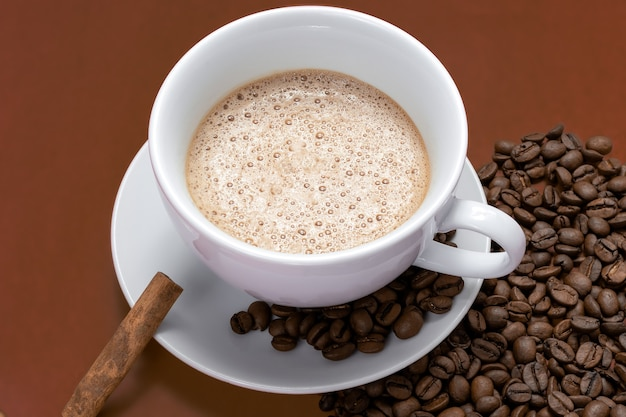 Cup with cappuccino and coffee beans and cinnamon on the side