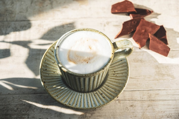 Cup with cappuccino coffee on a white wooden background with a shadow from tree leaves.