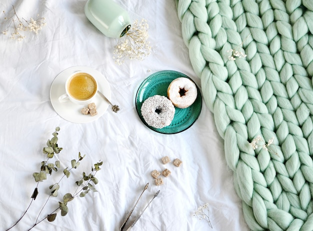 Cup with cappuccino doughnuts green pastel giant plaid bedroom morning