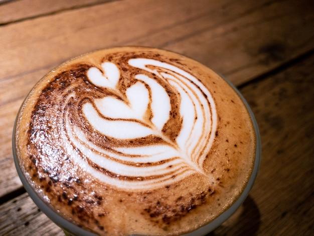 コーヒーハウスの黒い木製のテーブルにハート型のラテアートフォームとカプチーノのカップ。カフェの卓上で蒸し暑いカフェインドリンク。