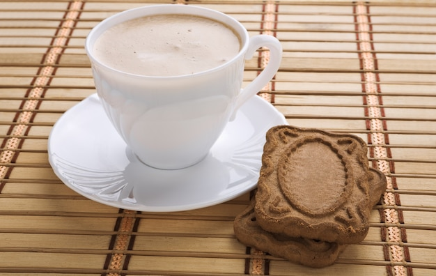 Cup with capuchino and cookie