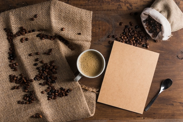 Cup with cardboard near sack with coffee beans and sackcloth
