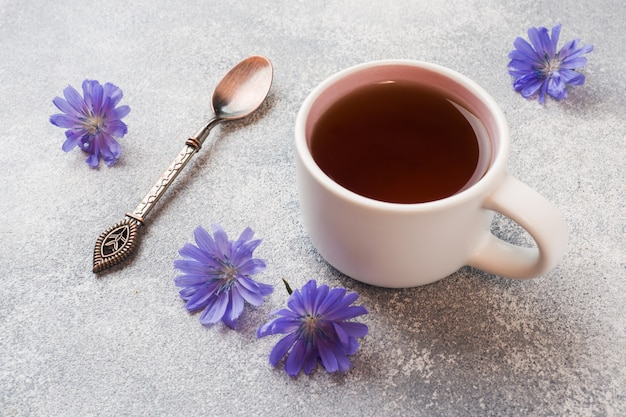 Cup with chicory drink and blue chicory flowers on grey table