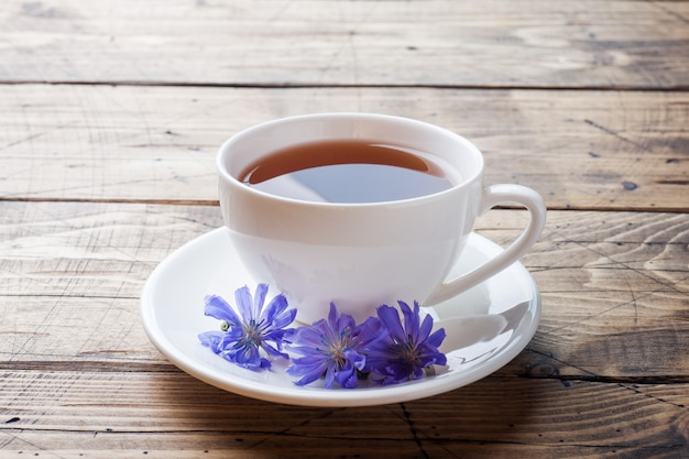 Cup with chicory drink and blue chicory flowers on wooden table