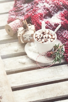 Cup with chocolate and marshmallows with a scarf with snow
