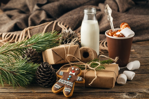 Cup with christmas hot chocolate drink, marshmallows and cinnamon on wooden bright table. holiday gift concept,