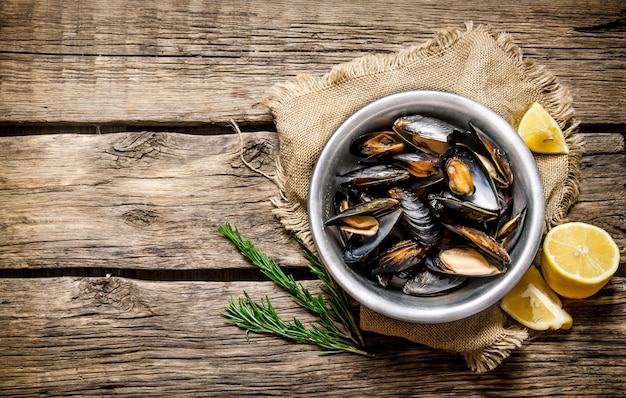 Cup with clams, limon and rosemary. on a wooden table.  free space for text . top view