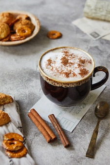 Cup with cocoa or coffee with milk cinnamon and cookies on a light gray surface