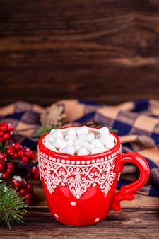 Cup with cocoa and marshmallows in cozy christmas decorations wooden background
