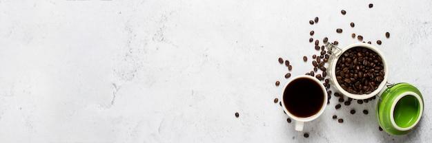 コーヒーの入ったカップ、コーヒー豆の缶、コーヒー豆がコンクリートの空間に点在しています。バナー
