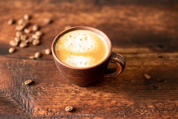나무 배경에 커피와 커피 콩을 넣은 컵.