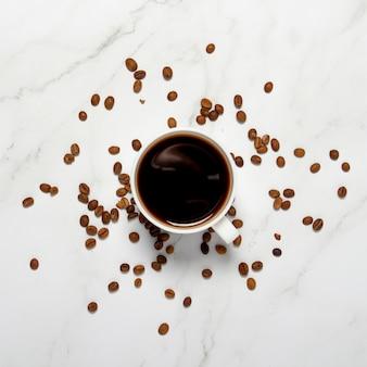 コーヒーと大理石のテーブルの上のコーヒー穀物のカップ。平方。コンセプトの朝食、ブラックコーヒー、夜のコーヒー、不眠症。フラット横たわっていた、トップビュー