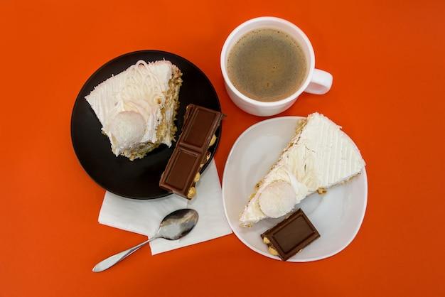 オレンジ色の背景でコーヒーとケーキとカップ