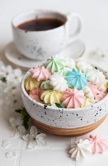 타일 배경의 그릇에 커피와 작은 머랭을 넣은 컵