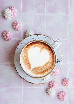 타일 배경에 커피와 작은 머랭을 넣은 컵