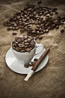 Чашка с кофейными зернами и сигарой на мешковине