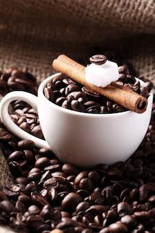 コーヒー豆とシナモンスティックのカップ
