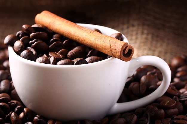 Cup with coffee beans and cinnamon stick