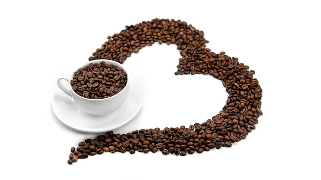 A cup with coffee beans in heart made of coffee beans. lots of coffee beans.